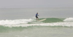 Longboarder surfing knee high wave on Pensacola Beach