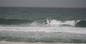 Surfers taking off on a wave by the Pensacola Beach Gulf Pier on June 2012