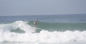 Cathy Harding of PensacolaSurf riding a wave on her longboard at the Cross on Pensacola Beach