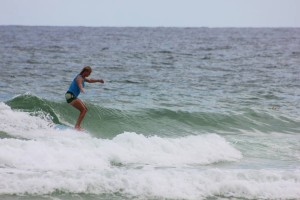 Cathy Harding hanging ten on her longboard while surfing at Pensacola Beach, FL