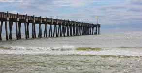 Pensacola Beach Gulf Pier with a yellow flag flying in hard offshore wind