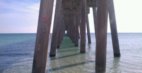 Pensacola Beach Gulf Pier underside with flat, clear Gulf of Mexico water